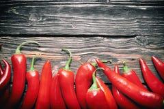 Chilipeppar på en tabell Fotografering för Bildbyråer