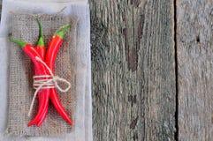 Chilipeppar på linnetextur och trätabellen, krydda Arkivbilder