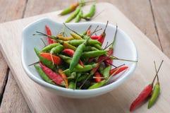 Chilipeppar, rått och lagat mat på en vit platta Royaltyfria Foton