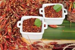 Chilipulver och torkade peppar på wood bakgrund Arkivbild