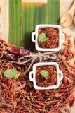 Chilipulver och torkade peppar på wood bakgrund Royaltyfria Bilder