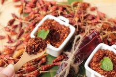 Chilipulver und getrocknete Pfeffer auf hölzernem Hintergrund Stockfoto