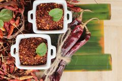 Chilipulver und getrocknete Pfeffer auf hölzernem Hintergrund Stockbild