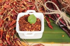 Chilipulver und getrocknete Pfeffer auf hölzernem Hintergrund Stockfotografie