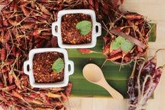 Chilipulver und getrocknete Pfeffer auf hölzernem Hintergrund Lizenzfreie Stockfotografie
