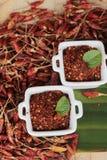 Chilipulver und getrocknete Pfeffer auf hölzernem Hintergrund Lizenzfreies Stockbild