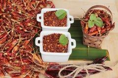 Chilipulver und getrocknete Pfeffer auf hölzernem Hintergrund Lizenzfreies Stockfoto