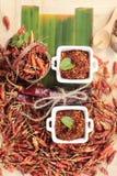 Chilipulver und getrocknete Pfeffer auf hölzernem Hintergrund Lizenzfreie Stockfotos