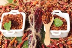 Chilipulver und getrocknete Pfeffer auf hölzernem Hintergrund Stockfotos