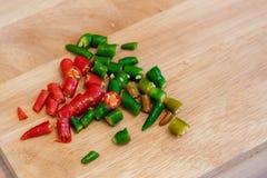 Chilis отрезка зеленые и красные на прерывая доске Стоковое Изображение