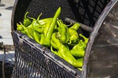 Chilis frescos do portal em um torrador exterior do tambor que prepara-se para ser cozinhado foto de stock