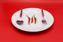 Chilis rojos en la placa blanca con los cubiertos y el fondo rojo Imagenes de archivo