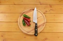 Chilis rouges et verts avec un couteau sur un hachoir Photos libres de droits