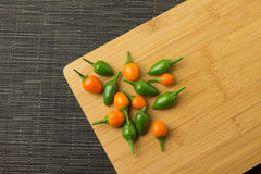 Chilis. Several colorful chilis on a wooden plate stock image