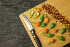 Chilis. Several colorful chilis on a wooden plate royalty free stock image