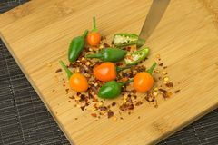 Chilis. Several colorful chilis on a wooden plate stock photo
