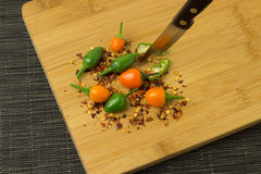 Chilis. Several colorful chilis on a wooden plate stock photos
