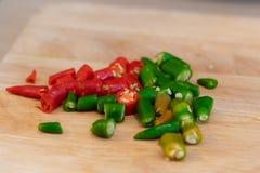 Chilis verdi e rossi del taglio sul tagliere Fotografia Stock Libera da Diritti