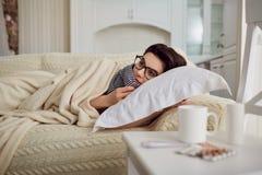 Chill женщина под одеялом на кровати в комнате Стоковое Фото