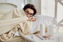 Chill женщина под одеялом на кровати в комнате Стоковая Фотография