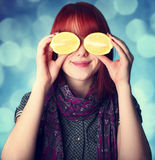 Chill girl in scarf keep lemon instead of eye.  Royalty Free Stock Photography