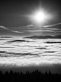 Chill inverse weather in winter mountains, heavy mist. Valley full of fog. Peaks of mountains above creamy mist stock photos