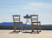 Chill out. Two chairs on terrace over beautiful blue sky in Oia stock photography