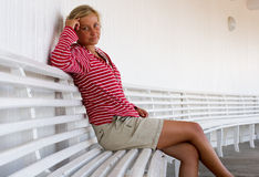 Chill out. A beautiful young woman sitting on a bench Royalty Free Stock Image