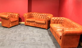 Chill out corner. Three leather sofas in the corner. Seats for 5 people. Red walls stock photo