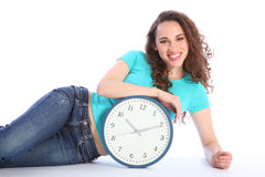 Chill out time for sexy happy girl with clock. Time to relax and chill out pose by sexy smiling girl lying on the floor with a large clock. She has long brown Royalty Free Stock Photography