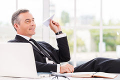 Chill time. Playful mature man in formalwear holding paper airplane and smiling while sitting at his working place Royalty Free Stock Photo