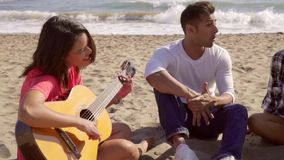 Chill To The Sounds Of The Guitar. Mixed-race group of young people sitting on the sandy beach and chill to the sounds of the guitar stock video footage