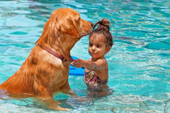 Chilld with dog in swimming pool Stock Photography