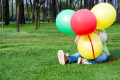 Chilld hiding behind balloons Stock Photo