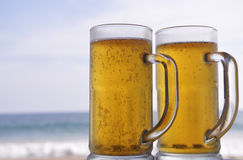 Chilled beer on a sunny day at the beach Stock Photos