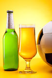 Chilled beer on yellow with ball Royalty Free Stock Image