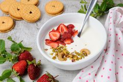 Chilled Buttermilk soup. From Greek yogurt with strawberries and pistachios, cashews. Serve with crispy biscuits. Vertical shot Stock Images