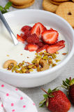 Chilled Buttermilk soup. From Greek yogurt with strawberries and pistachios, cashews. Serve with crispy biscuits. Vertical shot Royalty Free Stock Image