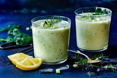 Creamy cold cucumber soup in glass. Chilled cucumber soup with yogurt, dill, lemon and ice cube royalty free stock images