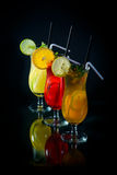 Chilled fruity cocktails on a black mirrored background with sli. Ces fruits Royalty Free Stock Photo