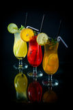 Chilled fruity cocktails on a black mirrored background with sli. Ces fruits Stock Images