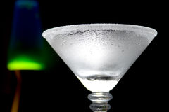 Chilled Martini Glass. Frosted or chilled Martini glass with the rim coated in sugar. Background contains large blue and green Lava Light royalty free stock photos