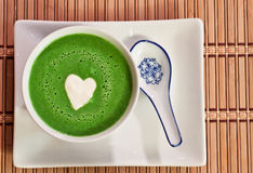 Chilled pea soup. View from the top of a bowl of chilled sweet pea soup garnished with a heart shaped cream drop in the middle royalty free stock photos