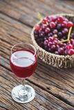 Chilled Red Grape Juice with fresh fruits. On old wood table background Stock Photography