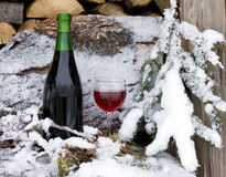 Chilled red wine. Bottle and glass of wine chilled by snow on a wood pile of firewood royalty free stock images