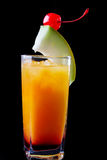 Chilled tropical rum and orange cocktail. With ice garnished with a slice of fresh melon and a maraschino cherry for a delicious refreshing appetizer over a royalty free stock photography