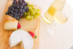 A chilled white wine. With grapes, cheeses and strawberries Royalty Free Stock Photo