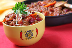 Chilli. Bowl of chili with beans, with cooking pan behind.  Delicious chili con carne Stock Images