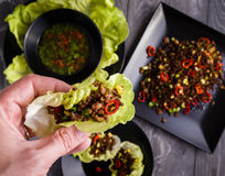 Chilli beef lettuce wraps. On black plate stock photography
