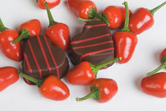 Chilli Chocolates. Red Chillies and Heart shaped chocolates on a white background royalty free stock photo
